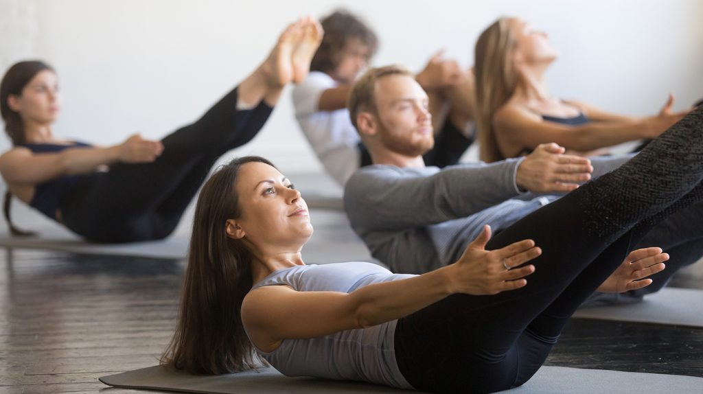 Yoga group class, 5 participants holding boat pose