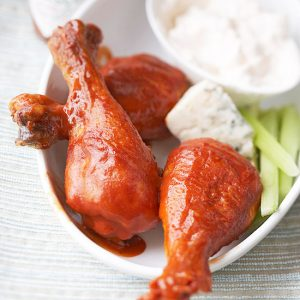Buffalo chicken wings on a white plate with blue cheese, celery and a bowl of ranch