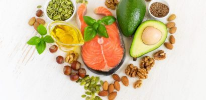 Foods With high omega 3's in the shape of a heart. Includes various nuts and seeds, salmon, avocados and olive oil.