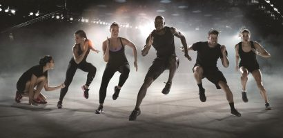High intensity interval training - 5 athletes performing side skaters with a coach motivating them.