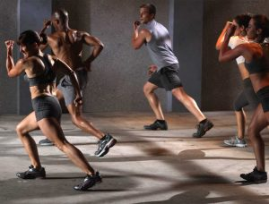 group fitness training - 5 athletes doing side lunges in a group class